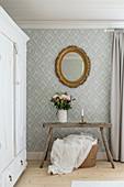 Weißer Kleiderschrank, rustikale Bank mit Blumenstrauß und Goldrahmenspiegel im Schlafzimmer