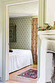 View of bed with with white cover in bedroom with patterned wallpaper
