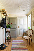 Plant stand and armchair in hallway with white-painted, wood-clad walls