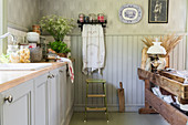 Grey cabinets and antique table in country-house kitchen
