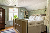 Bed made from reclaimed materials in bedroom with patterned wallpaper