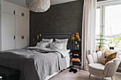 Double bed, white wardrobe and armchair in bedroom with dark grey wall