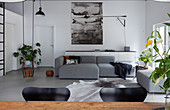 View over rustic dining table to grey sofa and child's swing in loft apartment