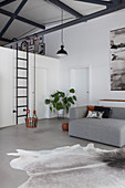 Grey sofa and child's swing in loft apartment