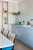 Kitchen counter with marble top next to dining table and bistro chairs