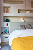 Double bed surrounded by modular shelving in bedroom