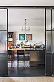 Open glass and steel door leading into industrial-style kitchen with black floor