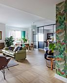 Open-plan, eclectic interior with parquet floor and sliding doors