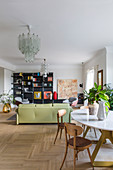 Dining table and sofa in open-plan living room in classic retro style