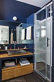 Kleines Bad mit blauen Wänden und Waschtisch aus Holz