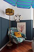 Sessel und maritime Deko an halbhoch blau gestrichener Wand