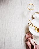 Geschirr, goldenes Besteck und Gläser auf zerknitterter Tischdecke