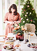 Frau am festlich gedeckten Tisch in Nude-Tönen zu Weihnachten