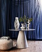 Verschiedene Vasen auf rundem Tisch vor dunkelblauem Vorhang