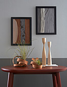 Artworks made from wooden veneers on grey wall and sculptural vases on table