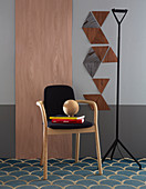 Chair in front of wooden panel next to triangles of wooden veneer on grey wall