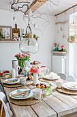 Frühlingshaft gedeckter Tisch im Esszimmer mit rustikaler Deko