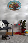 Modern chair and red side table against graphic wallpaper