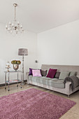 Grey sofa with scatter cushions, standard lamp and serving trolley in living room