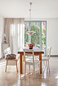Esstisch aus Holz mit weißen Stühlen und Sitzbank