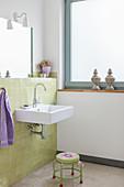 Badezimmer mit grünen Wandfliesen und Fenster