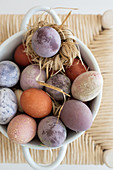 Easter eggs coloured using natural dyes in straw nest