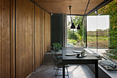 Wood-clad dining area with panoramic windows