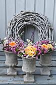 Sommersträuße aus Rosen, Scheinwaldmeister und Schleierkraut in kleinen Betonspindeln von Kranz aus weiß gefärbten Ranken