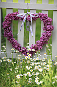 Heart wreath made of lilac blossoms for Mother's Day hung on the fence, with a flower meadow with daisies