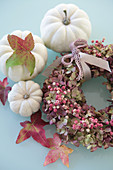 White pumpkins, sweetgum leaves and wreath of hydrangea flowers and pink pepper