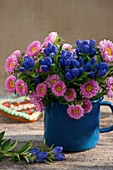 Closed Gentiana with summer asters in an enamel pot