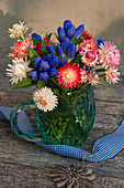 Closed Gentiana with strawflowers in a mug