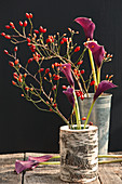 Rosehips and Calla lilies in birch trunk and zinc cups