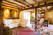 Sofa set and rocking chair in open-plan interior with rustic wood-beamed ceiling