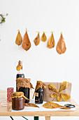 Einmachgläser und Geschenk mit Herbstlaub dekoriert