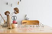 Plätzchenausstecher, Garn, Teelicht und Vase mit Trockenblume auf Tisch