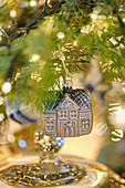 House-shaped Christmas bauble hanging from branch