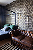 Classic leather sofa against patterned wallpaper in bedroom