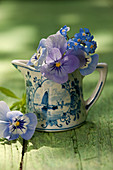 Pansies and forget-me-not blossoms in ceramic jugs