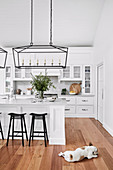 Weiße Küche mit Kücheninsel, schwarzen Barhockern und Hängelampe