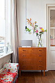 Flowers on retro chest of drawers below pendant lamp next to window