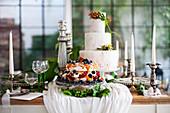 Zwei Festtagstorten auf festlich gedecktem Tisch mit Kerzenständern und Weingläsern