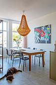 Hängelampe über Esstisch mit Stühlen vor moderne Kunst an der Wand, im Vordergrund Hund auf Fliesenboden