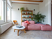 Pink sofa set in front of shelves, round coffee table and herringbone parquet flooring in living room