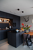 Fitted kitchen and island counter with dark cabinets, dining table and chairs
