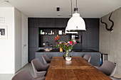 Dining table with solid wooden top and elegant chairs in front of kitchen with dark cabinets