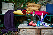 Old wooden trunk used as table and bench with colourful cushions in romantic ivy-covered arbour