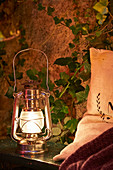 Storm lamp on wooden bench with cushions in garden