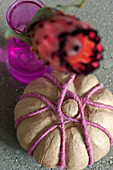 Fake pumpkin decorated with woollen yarn and blurred protea flower