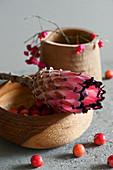 Protea-Blüte mit Zieräpfeln und Pfaffenhütchen